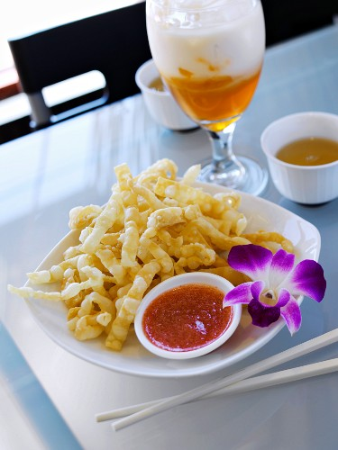 Crispy, Deep-fried Noodles with Chili Dipping Sauce and Orchid Garnish