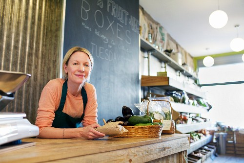 Grocer working behind counter at store
