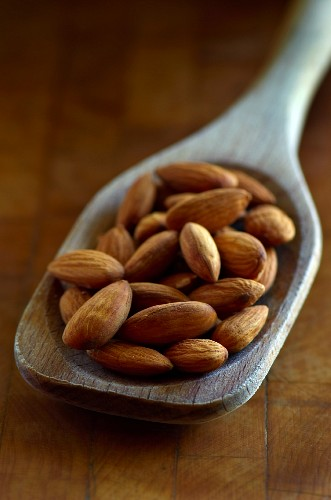 Whole Almonds in a Wooden Spoon