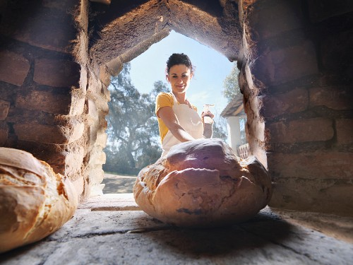 Woman taking bread out of wood oven