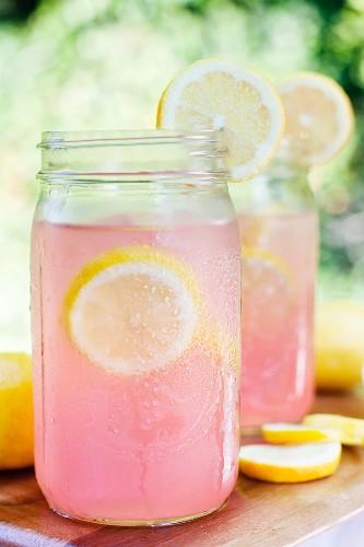 Pinkfarbene Limonade in Schraubgläsern mit Zitronenscheiben