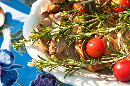 Pork chops with rosemary and cherry tomatoes on a serving platter