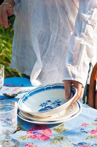 Frau stellt Teller auf Gartentisch