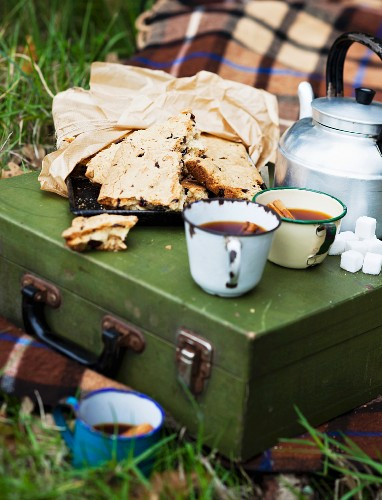 An autumn picnic with cake and hot drinks on a picnic hamper