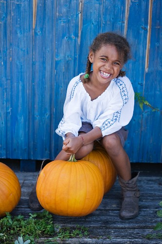 A little girl sitting on a big pumpkin