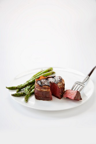 Bacon Wrapped Filet Mignon; Piece Pierced on a Fork; Asparagus
