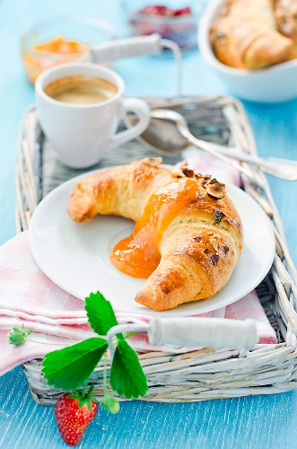 A croissant with apricot jam and coffee for breakfast