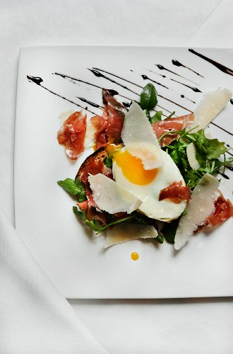 Arugula with Fried Egg, Prosciutto, Shaved Parmesan, Toast and Balsamic Reduction