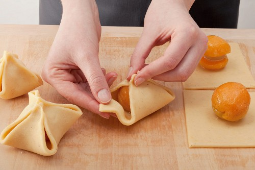 Hands filling pastry parcels with apricots