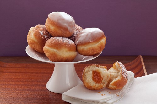 Several doughnuts on a cake stand, and one doughnut, broken open, on a white napkin
