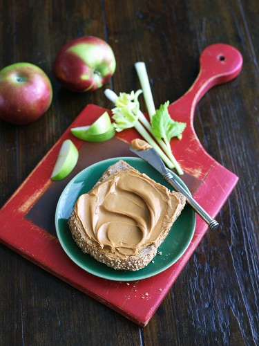 Peanut Butter on a Slice of Whole Wheat Bread with Apples and Celery