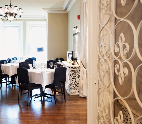 Elegant hotel restaurant with white wrought iron gate and parquet floor of exotic wood