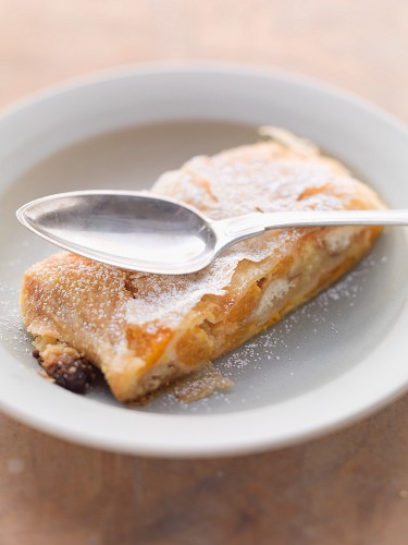 A slice of apricot strudel with a spoon