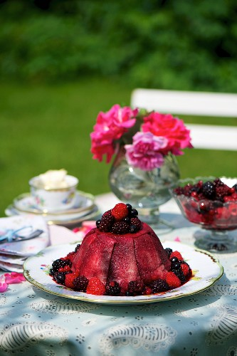 Summer pudding with blackberries on a table in the garden