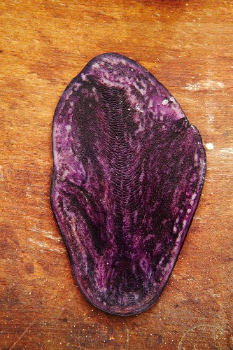 A slice of a Vitelotte potato on a wooden surface