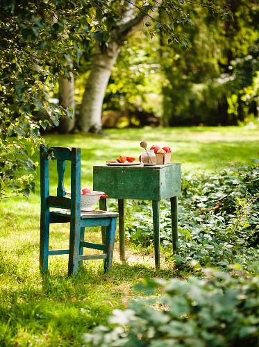 Pfirsiche auf einem alten Tisch und Stuhl im Garten