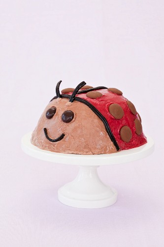 A Lady Bug Ice Cream Cake on a Pedestal Dish