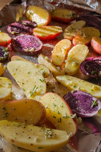 Fingerling and Peruvian Purple Potatoes Seasoned and Ready for Baking on a Foil Lined Pan