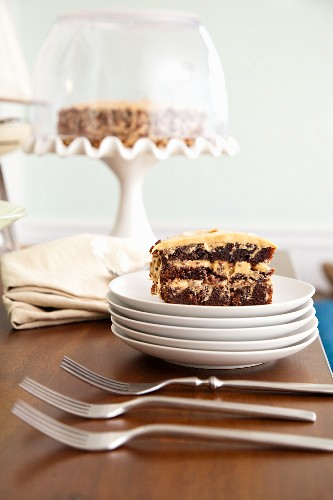 Salted Caramel Chocolate Cake Slice on Stacked White Plates; Forks
