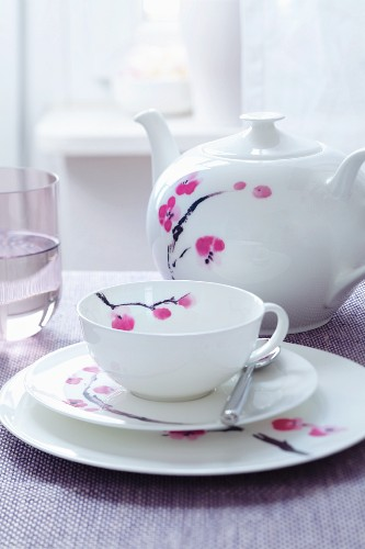 A place setting for afternoon tea and a teapot, all decorated with a flower motif