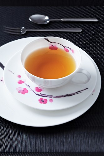 A place setting for afternoon tea, with a flower design, on a black surface