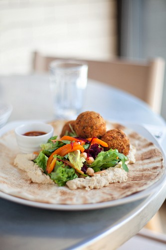 Falafels with chickpea purée and salad on flatbread