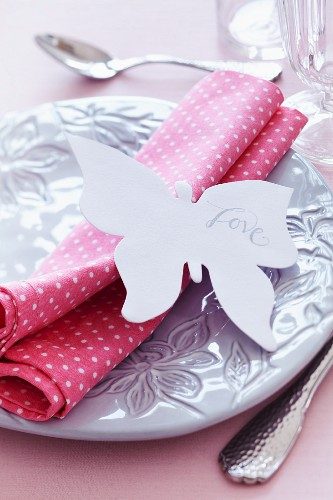Place setting with napkin & 'Love' written on paper butterfly