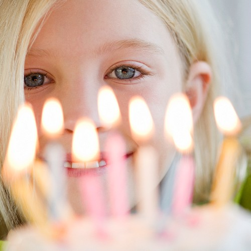 USA, New Jersey, Jersey City, Girl (8-9) in front of birthday cake