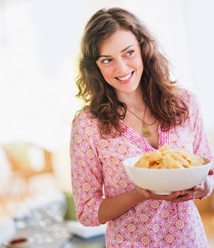 Woman carrying bowl with snacks
