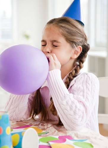 Young girl blowing up balloon