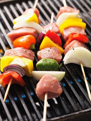 Raw shish kebab skewers on the barbecue