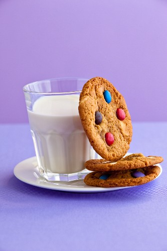Cookies with M&Ms (chocolate candies) and a glass of milk