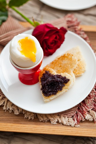 Soft boiled egg with caviar on toast 'hearts'