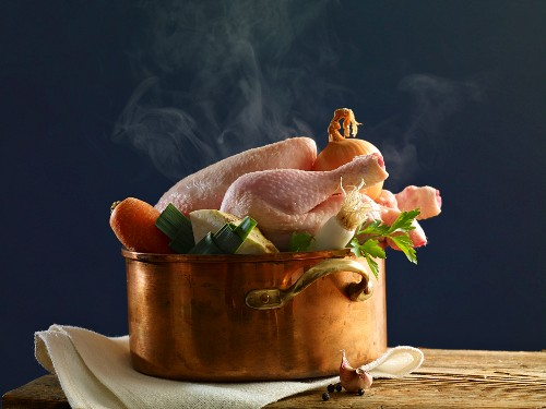 Stewing chicken with vegetables in a copper pot