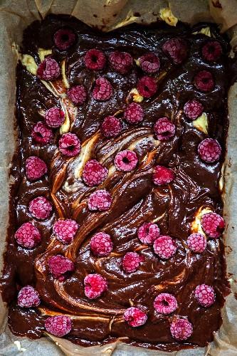 Chocolate and raspberry brownie cheesecake before baking (close-up)