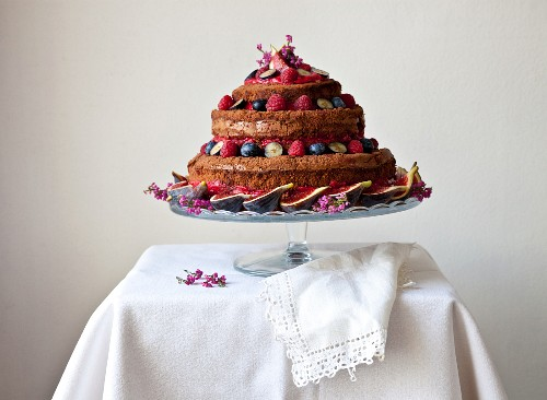 A naked birthday cake with fresh figs and berries