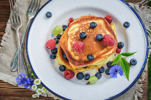 A pile of pancakes with fresh berries and maple syrup (seen from above)