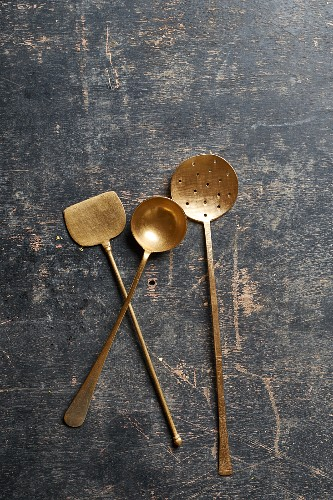 A copper turner, ladle and strainer spoon