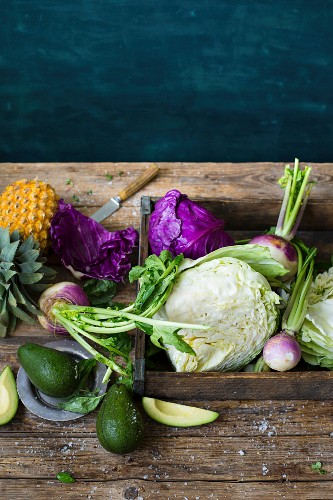 A still life with red cabbage, pineapple, avocado and turnips on a wooden table
