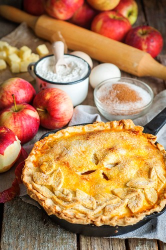 Apple pie with a pastry topping, surrounded by the ingredients
