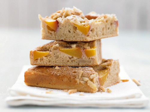 Peach cake on a plate with buttermilk and almonds