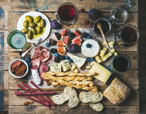 Various wines in glasses, meat variety, bread, sun-dried tomatoes, honey, green olives, figs, nuts and berries