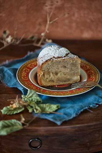 A slice of pear cake dusted with icing sugar