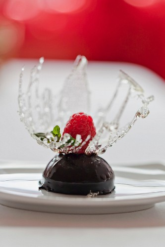Chocolate dessert served with raspberry and sugar decoration