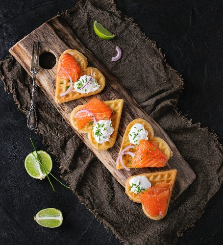 Wafers as heart shape with salted salmon, red onion, chive, lime and ricotta cheese on wooden cutting board