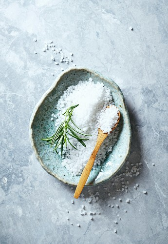 Natural bath salt with a sprig of rosemary
