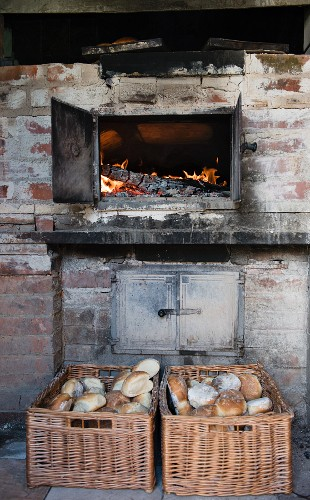 A glowing wood stove and freshly baked bread rolls in wicker baskets