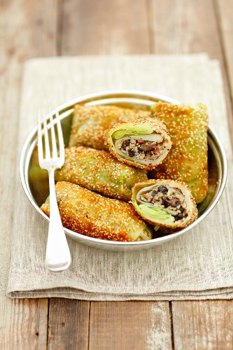Fried cabbage roulades filled with mushrooms, bacon and millet