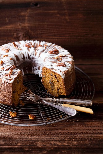 Pumpkin cake with pecan nuts on a cooling rack