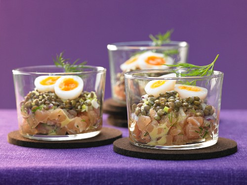 A salmon steak with lentils, quail eggs and honey mustard sauce